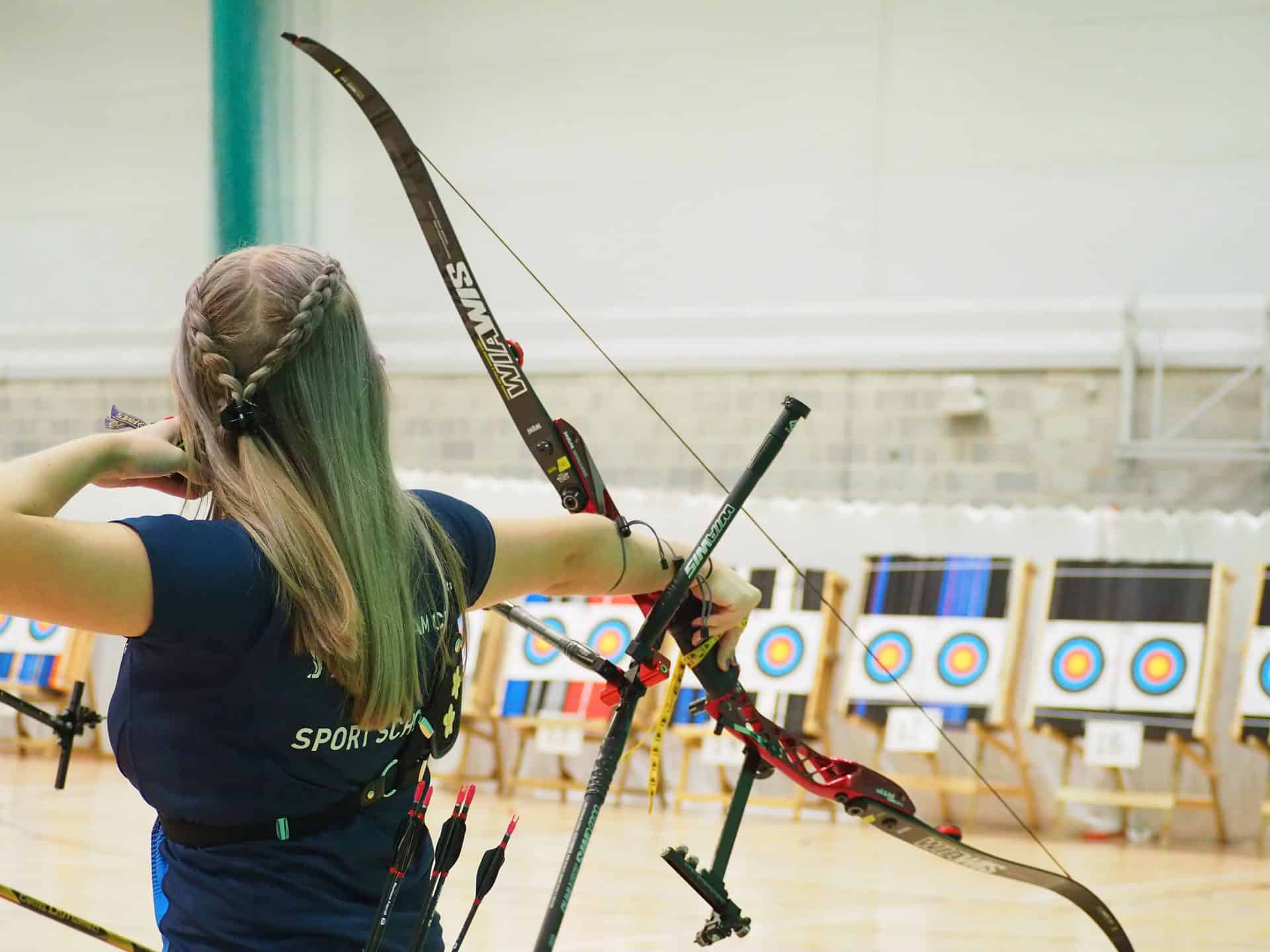 Female archer shooting indoors