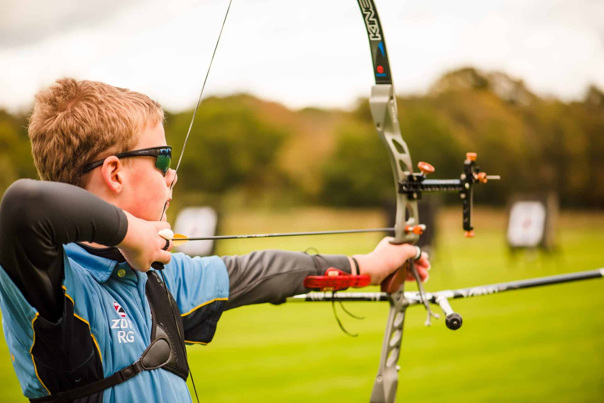 Young male archer shooting at outdoor range