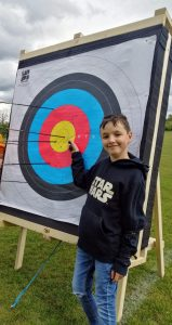 Young boy with archery target