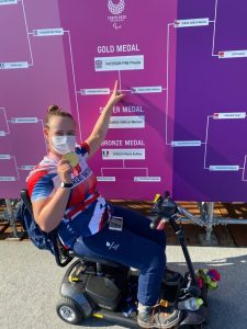 Phoebe Paterson Pine in front of the tournament board after winning gold at Tokyo 2020